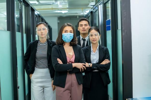 ビジネスチームは、オフィスで腕を組んで立っている社会的距離政策として働いている医療の顔のマスクを着ています。