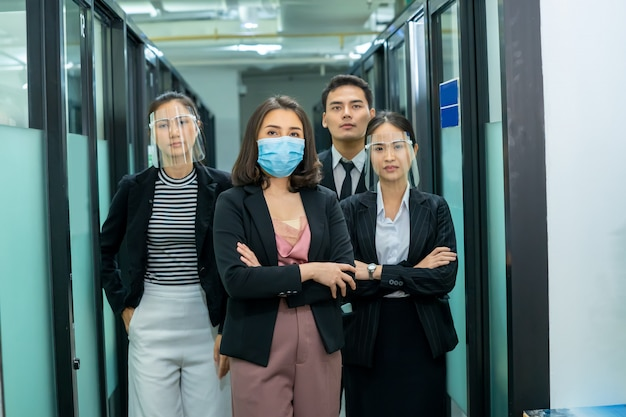 Business team wearing medical facial mask working as of social distancing policy standing with arms crossed in the office.