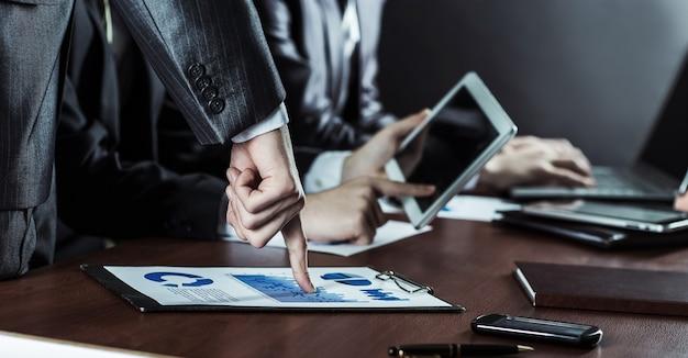 オフィスの職場向けのデジタルタブレットと財務チャートを備えたビジネスチーム