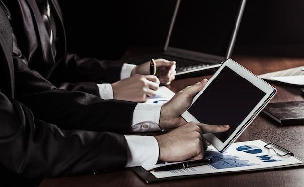 オフィスの職場向けのデジタルタブレットと財務チャートを備えたビジネスチーム。