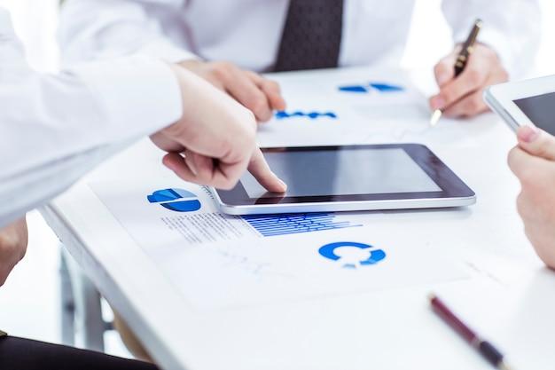財務チャートを扱うデジタルタブレットとスマートフォンのビジネスチーム