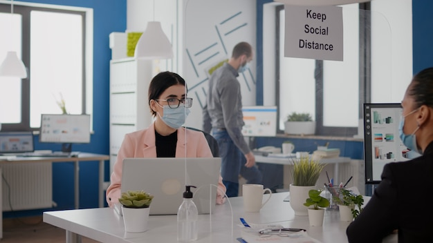 Business team with face masks planning marketing project while looking into monitor for statistics sitting in new normal office. coworkers respecting social distancing during coronavirus global pandem