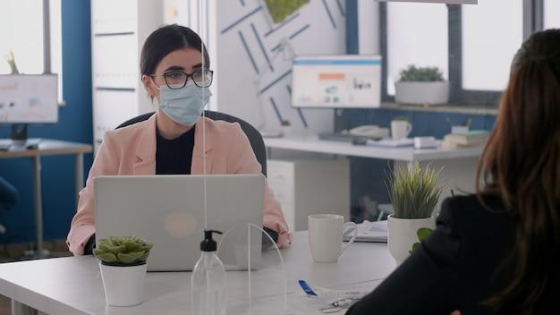 新しい通常のオフィスに座っているコンピューターのディスプレイを調べながら、マーケティングのアイデアに取り組んでいるフェイスマスクを持つビジネスチーム。コロナウイルスの世界的大流行の間の社会的距離を尊重する同僚
