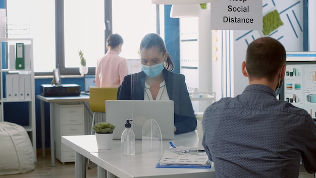 Business team with face masks working in company office taking precaution to mantain safety measures to avoid coronavirus infection. collegues respecting social distancing during covid19 quarantine