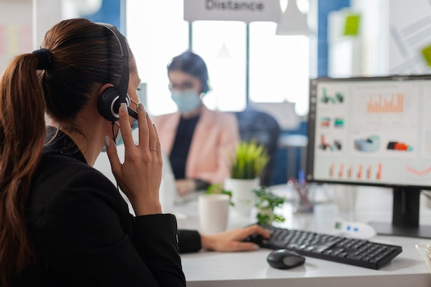 Деловая команда с гарнитурой разговаривает в микрофон, проверяет финансовую статистику в новом обычном офисе компании. сотрудники бригады носят защитные маски для лица, чтобы предотвратить заражение коронавирусом.