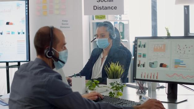 Деловая команда с гарнитурой разговаривает в микрофон, проверяя финансовую статистику в новом обычном офисе компании. работники команды в защитных масках для предотвращения заражения коронавирусом