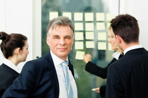 Бизнес-команда с лидером в офисе