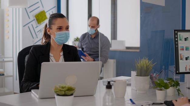 Деловая команда с медицинскими масками работает вместе в офисе стартап-компании во время глобальной эпидемии коронавируса. команда проверяет бизнес-отчеты, сохраняя социальное дистанцирование
