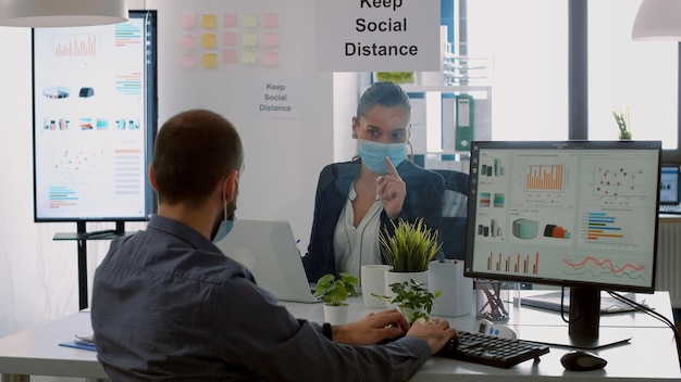Деловая команда с защитными масками для лица работает вместе в офисе компании во время глобальной пандемии коронавируса. коллеги сохраняют социальное дистанцирование, когда набирают на компьютере и проверяют отчеты