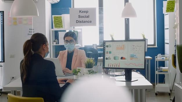 Деловая команда с защитными масками работает вместе в офисе стартап-компании во время глобальной пандемии коронавируса. команда проверяет финансовые отчеты, соблюдая социальное дистанцирование