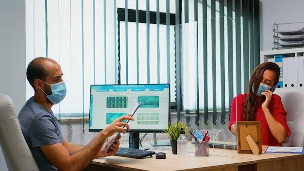 プレキシガラスを使用した社会的距離を尊重する保護マスクを備えたビジネスチーム。新しい通常のオフィスの職場で働いているフリーランサーは、コンピューターで検索してクリップボードに書き込みを話します。