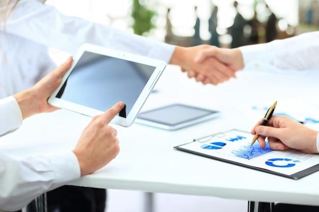Деловая команда с планшетом и документами на фоне деловых партнеров