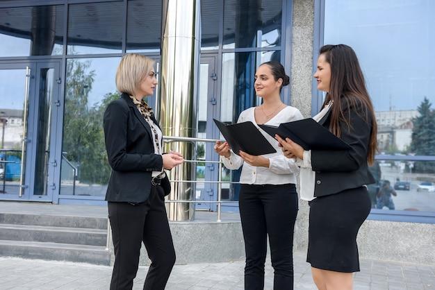 オフィスビルの外でポーズをとるタブレットを持つビジネスチーム