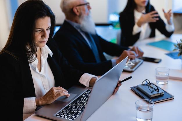 은행 방 안에서 회의를 하는 비즈니스 팀 직원 - 성숙한 여성의 얼굴에 초점