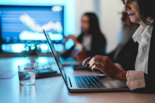 Работник бизнес-группы делает анализ фондового рынка в офисе хедж-фонда - внимание на руку женщины