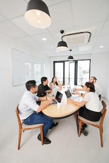 Деловая команда, работающая в зале заседаний