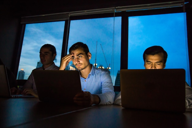 Business team working late at night with lights off and computers laptop screen light on.
