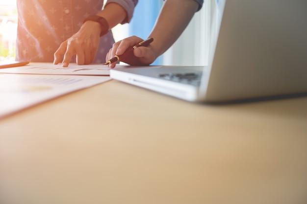 Бизнес-группа работает над новым бизнес-планом с современным цифровым компьютером с copyspace.