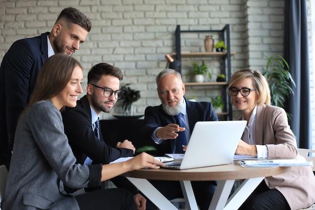 Бизнес-группа, работающая на ноутбуке, чтобы проверить результаты своей работы.
