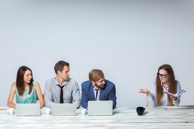 Бизнес-группа, работая вместе в офисе на светло-сером фоне. все работает на ноутах. босс читает тетрадь. изображение copyspace