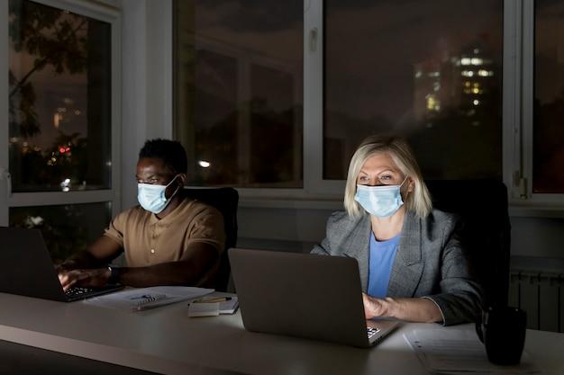 医療用マスクを着用しながらオフィスで遅くまで働くビジネスチームメイト