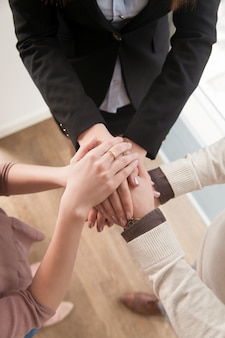 Business teamwork concept, top view of hands joined together, vertical