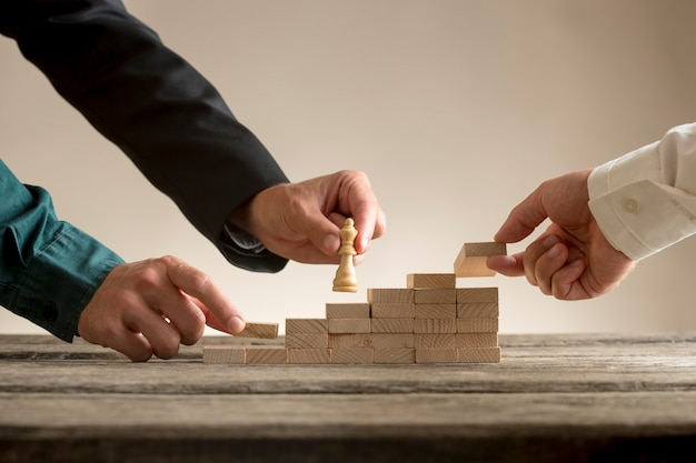 Business teamwork concept with a businessman moving a chess piece up a series of steps