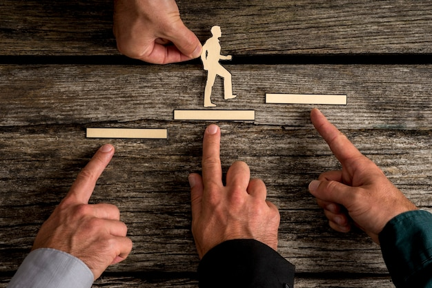 Business teamwork and cooperation concept with the hands of four businesspeople supporting paper cut outs of a man climbing the steps to success over rustic wood background