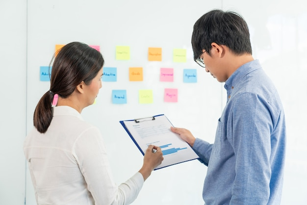 회의에서 비즈니스 팀워크 및 몇 가지 아이디어 브레인 스토밍 계획을 수집하기 위해 사무실 방에서 팀과 논의하는 미러 보드에 접착 스틱 노트.