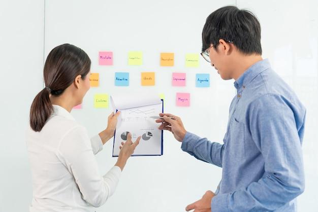 会議でのビジネスチームワークと、アイデアのブレーンストーミング計画を収集するためにオフィスルームのチームと話し合うミラーボード上の粘着性の付箋。