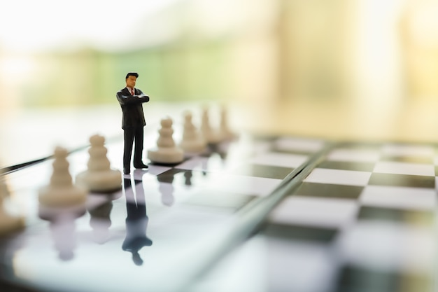 Business, teamwork and strategy planning concept.  close up of businessman miniature people figure standing on chessboard between pawn chess pieces and copy space.