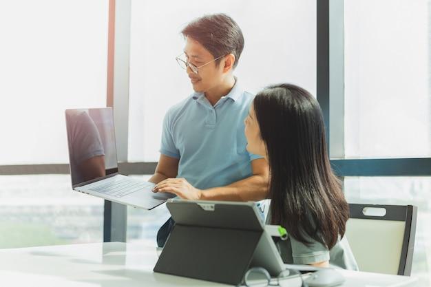 노트북을 들고 있는 남자와 사무실에서 일하는 비즈니스 팀워크.