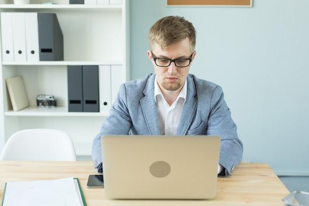 Бизнес, технологии и люди концепции - красивый человек, работающий в офисе на ноутбуке.