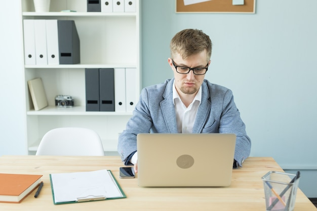 Business, technologies and people concept - handsome man working in office on laptop.