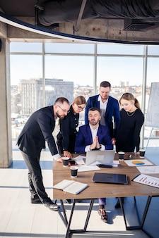ビジネス、テクノロジー、オフィスのコンセプト-ラップトップコンピューター、ドキュメント、コーヒーを扱う幸せなビジネスチーム。営業日の開始前に会議を開き、事業計画について話し合う