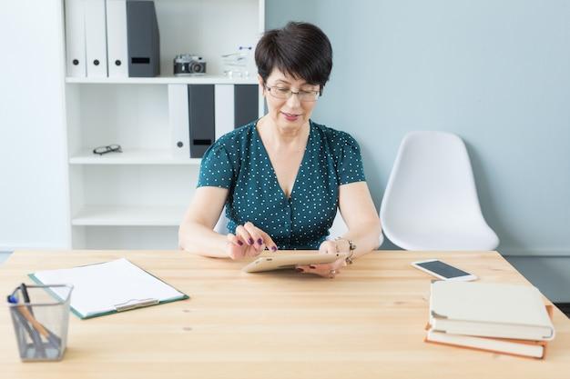 Концепция бизнеса, технологий и людей - женщина средних лет, использующая гаджет в офисе