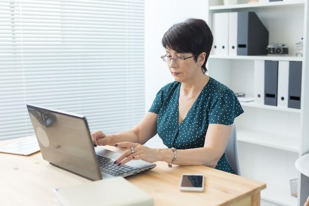 Концепция бизнеса, технологий и людей - женщина средних лет работает в офисе и использует ноутбук