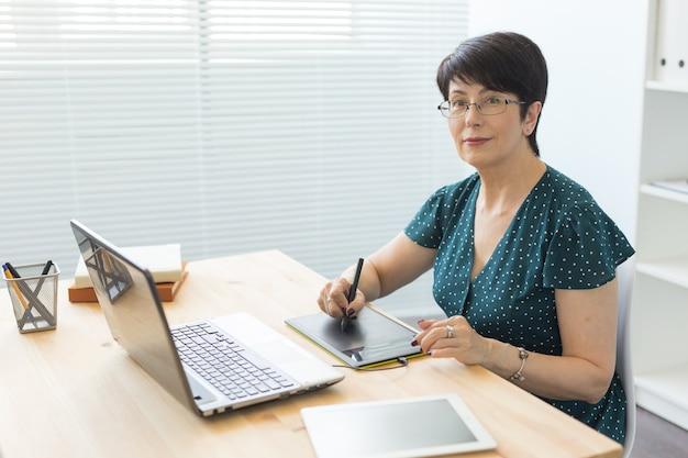 ビジネス、テクノロジー、人々のコンセプト-女性はラップトップでの作業にスタイラスを使用します。