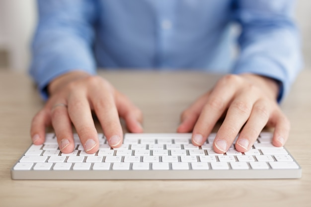Business and technology concept - close up of hands and keyboard on the table