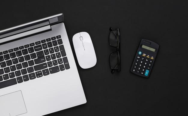 ビジネステーマ。黒の背景に電卓とメガネを搭載したノートパソコン。上面図