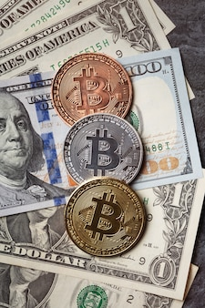 Business top view design concept of cryptocurrency bitcoin with usd dollar paper currency money over dark black table background.