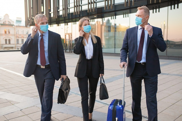 Business tourists in face masks travelling with briefcases or suitcase, walking outdoors, talking to each other. front view. business trip and epidemic concept