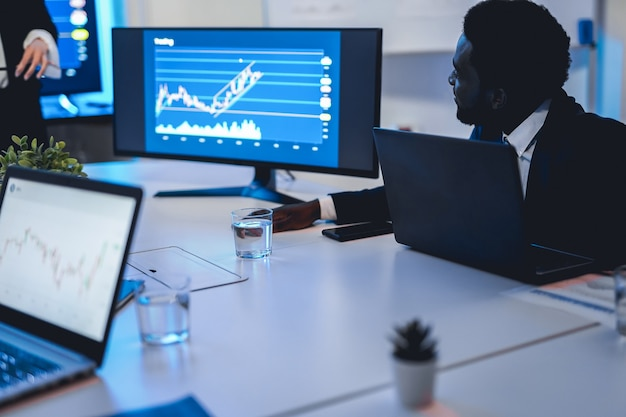 헤지 펀드 사무실에서 블록체인 분석을 하는 비즈니스 트레이더 팀 - 아프리카 남성의 얼굴에 초점