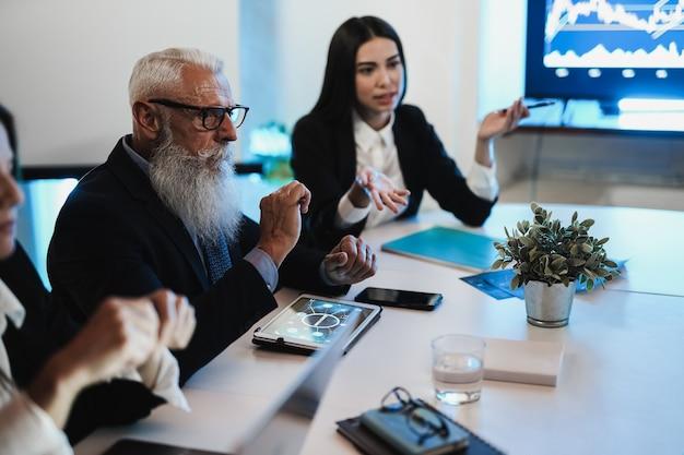 Команда бизнес-трейдеров проводит анализ блокчейна в офисе хедж-фонда - основное внимание уделяется левой руке женщины