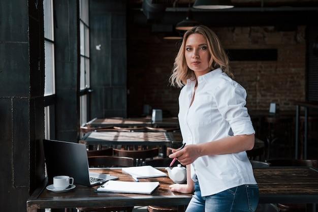 ビジネス研修。昼間のカフェで室内に金髪の巻き毛を持つ女性。