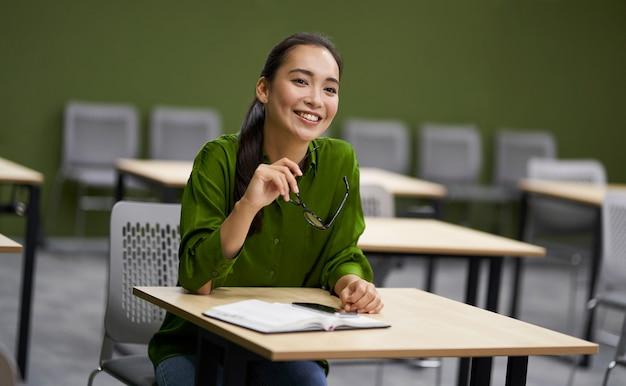Бизнес-подготовка молодая счастливая женщина офисный работник женского пола, сидя за столом в офисе и