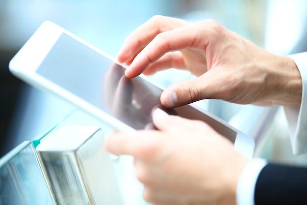 Деловые поездки - бизнесмен, использующий цифровой планшет в зале вылета аэропорта