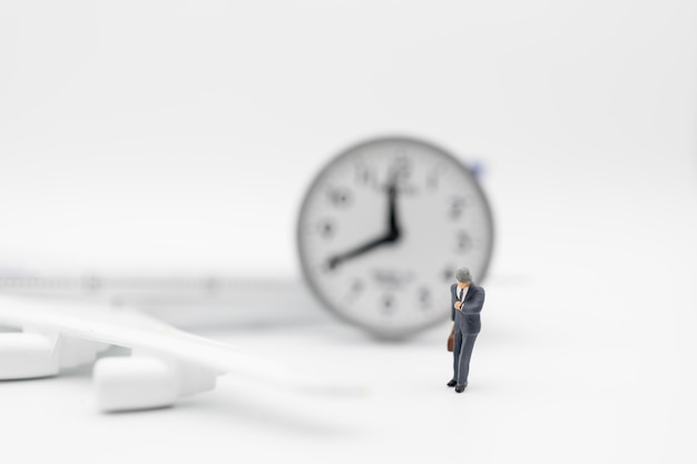 Business travel, time concept. close up of businessman traveler miniature figure with suitcase baggage looking to watch with mini toy airplane model and round clock on white background.
