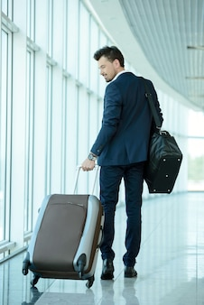 Business traveler pulling suitcase and holding passport.