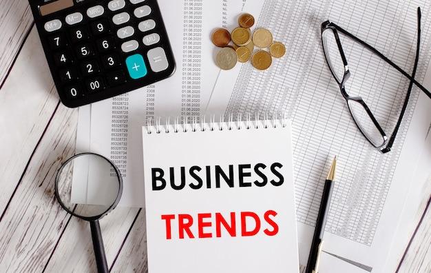 Бизнес-тенденции, записанные в белом блокноте рядом с калькулятором, наличными, очками, увеличительным стеклом и ручкой. бизнес-концепция.